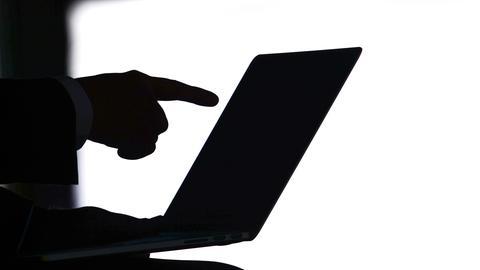Silhouette eines Menschen vor einem Laptop