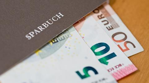 Ein Bündel Geldscheine liegt in einem Sparbuch