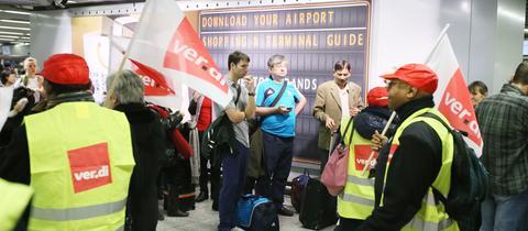 Reisende warten am Frankfurter Flughafen, während protestierende Verdi-Mitglieder an ihnen vorbeiziehen.