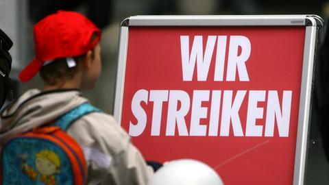 """Junge vor einem Schild mit der Aufschrift: """"Wir streiken."""""""
