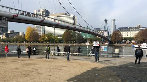 Menschenkette als Protestaktion von verdi am Mainufer
