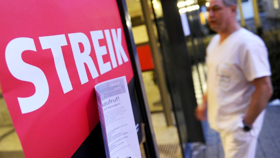 Foto eines Streikaufrufs in Form eines Posters von verdi an einem Klinikeingang. Im Hintergrund ist ein Pfleger zu sehen.