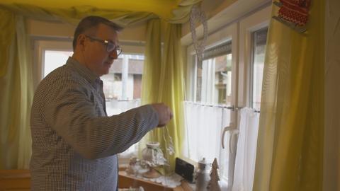 Steffen Lorey hängt eine Lichterkette ans Fenster.