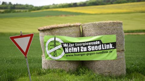 Auf Heuballen an einer Straße in Nordhessen prangt ein Transparent der Gegner der Stromtrasse Suedlink.