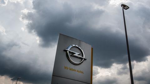 Opel-Symbol auf einer Stele vor dem Werk in Rüsselsheim - aus der Froschperspektive fotografiert. Darüber schwebt eine dunkle Wolke am Himmel.