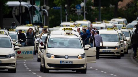 Taxis fahren im Protest-Konvoi durch die Innenstadt von Kassel.