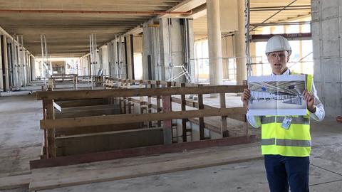 Fraport-Sprecher Christian Engel steht in der Baustelle von Flugsteig H - in den Händen hält er das Bild einer Visualisierung, wie das Gebäude aussehen wird.
