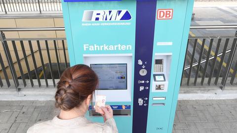 Kundin steht an Fahrkartenautomat