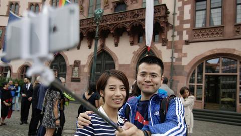 Asiatische Touristen machen ein Selfie vor dem Römer.