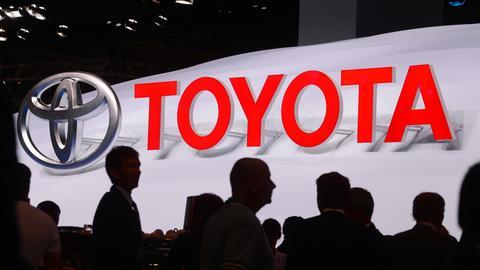 Toyota-Schriftzug und Log - davor Menschen - Aufnahme aus dem Jahr 2013