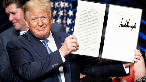 US-Präsident Donald trump hält eine von ihm unterschriebene Urkunde in die Luft