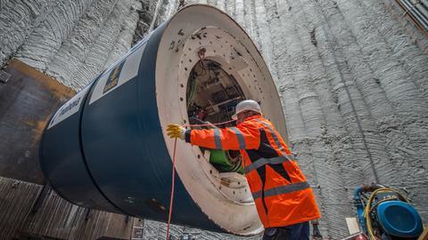 In der Baugrube zieht ein Tunnelbauer die Bohrmaschine in die richtige Position.