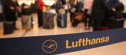 Wartende Passagiere stehen am Flughafen vor einem Service-Schalter der Lufthansa.