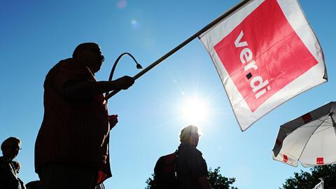 Ein Mann hält eine Verdi-Fahne in der Hand.