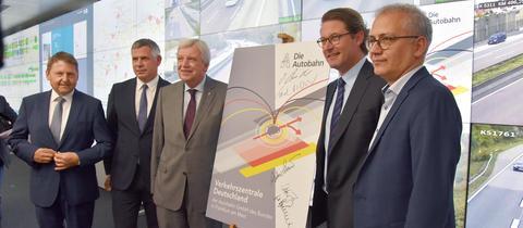 Bouffier, Scheuer, Al-Wazir mit Schild vor Monitorwand