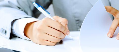 Eine Hand mit Stift unterschreibt Papiere.