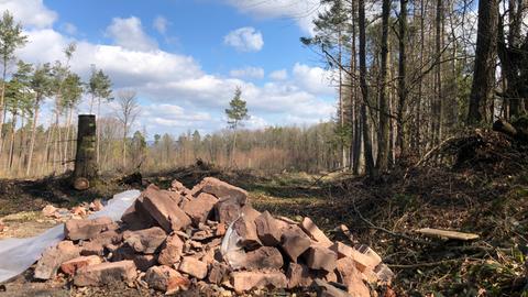 Ein Haufen mit Backsteinen und Plastikplanen im Wald