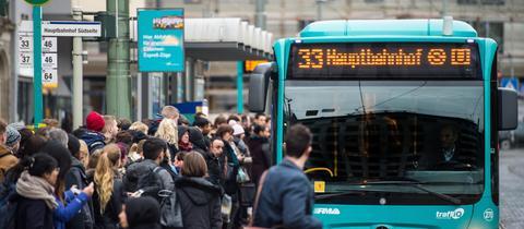 Viele Menschen warten an einer Haltestelle auf einen Bus der Nummer 33.