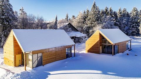 Wasserkuppen-Ferienhäuser aus Holz im Schnee
