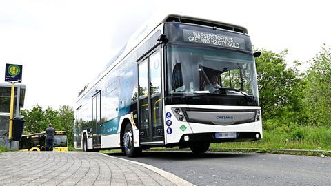 """Ein weißer Wasserstoff-Bus mit etwas höherem Dach steht an einer Haltestelle. Auf der Anzeige steht """"Wasserstoffbus H2.City Gold""""."""