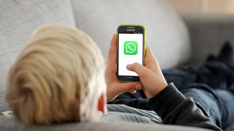 Symbolbild: Kind mit Smartphone, auf dem ein WhatsApp-Symbol leuchtet