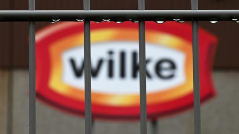 Firmenschild des nordhessischen Wurstproduzenten Wilke, durch Gitterstäbe fotografiert.
