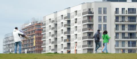 Spaziergänger sind in einem Neubaugebiet in Frankfurt unterwegs.