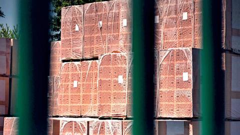 Hinter einem Tor stehen mehrere hochgestapelte Paletten Ziegelsteine