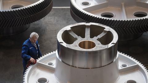 Ein Arbeiter prüft Zahnräder in einem Industriebetrieb.