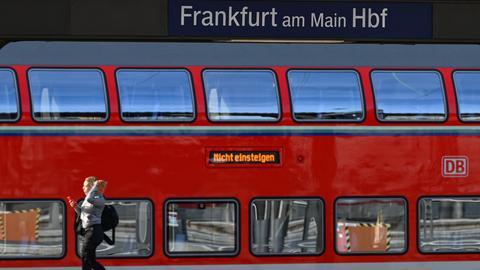 """Eine Frau geht im Frankfurter Hauptbahnhof an einem Regionalzug vorbei, auf dem """"Nicht einsteigen"""" steht."""