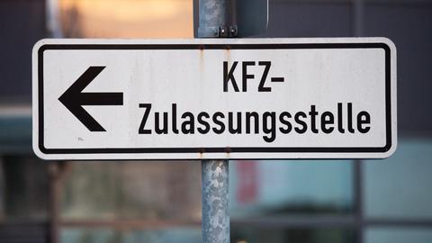 Ein Schild, das den Weg zu einer KFZ-Zulassungsstelle leitet.